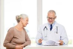 Uśmiechnięta starsza kobieta i lekarki spotkanie zdjęcia royalty free