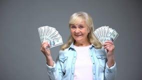 UÅ›miechniÄ™ta starsza kobieta pokazuje dolarowych banknoty, szybka pożyczkowa usÅ'uga, deponuje pieniÄ…dze zdjęcie royalty free