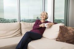 Uśmiechnięta starsza kobieta relaksuje na kanapie w domu z kawowym kubkiem Zdjęcie Stock