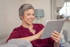 Uśmiechnięta starsza kobieta używa cyfrową pastylkę zdjęcie stock