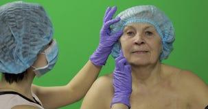 U?miechni?ta starsza kobieta w ochronnym kapeluszu Chirurg plastyczny sprawdza kobiety twarz zbiory wideo