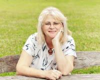 Uśmiechnięta starsza kobieta w parku Zdjęcia Royalty Free