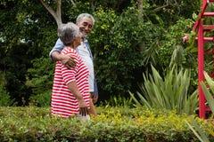Uśmiechnięta starsza para chodzi wpólnie wśród rośliien Zdjęcie Stock