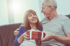 Uśmiechnięta starsza para wymienia prezent Zdjęcia Royalty Free