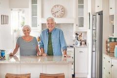 Uśmiechnięta starsza pary pozycja przy ich kuchennym kontuarem w domu obrazy stock