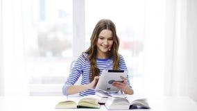 Uśmiechnięta studencka dziewczyna z pastylek książkami i komputerem osobistym zdjęcie wideo