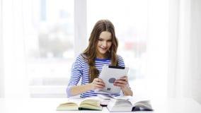 Uśmiechnięta studencka dziewczyna z pastylek książkami i komputerem osobistym zbiory