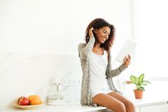 Uśmiechnięta szczęśliwa afro amerykańska kobieta używa komputer osobisty pastylkę Zdjęcia Royalty Free