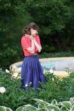 Uśmiechnięta szczęśliwa caucasian dorosła kobieta relaksuje w jej ogródzie z kwitnieniem kwitnie obrazy royalty free