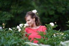 Uśmiechnięta szczęśliwa caucasian dorosła kobieta relaksuje w jej ogródzie z kwitnieniem kwitnie zdjęcie royalty free