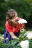 Uśmiechnięta szczęśliwa caucasian dorosła kobieta relaksuje w jej ogródzie z kwitnieniem kwitnie fotografia stock