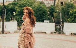Uśmiechnięta szczęśliwa dziewczyna w sukni, kapeluszu na miasto ulicie i patrzeć kamerę w kapeluszu, sukni w kwiacie i kurtce, obrazy royalty free