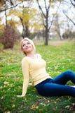 Uśmiechnięta szczęśliwa młoda dziewczyna siedzi outdoors patrzeć zdjęcia stock