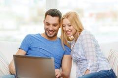 Uśmiechnięta szczęśliwa para z laptopem w domu Obraz Stock