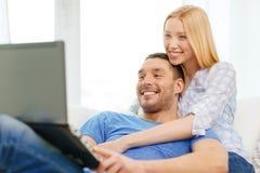 Uśmiechnięta szczęśliwa para z laptopem w domu Zdjęcia Stock
