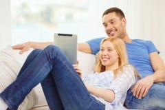 Uśmiechnięta szczęśliwa para z pastylka komputerem osobistym w domu Obraz Stock