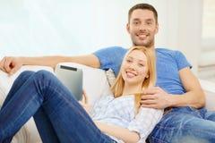 Uśmiechnięta szczęśliwa para z pastylka komputerem osobistym w domu Obrazy Royalty Free