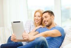 Uśmiechnięta szczęśliwa para z pastylka komputerem osobistym w domu Fotografia Stock
