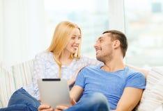 Uśmiechnięta szczęśliwa para z pastylka komputerem osobistym w domu Zdjęcia Royalty Free