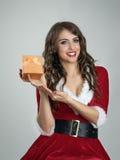 Uśmiechnięta szczęśliwa Santa dziewczyna pokazuje Bożenarodzeniową teraźniejszość w małym złotym pudełku z faborkiem Zdjęcie Stock