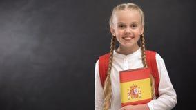 Uśmiechnięta uczennica trzyma Hiszpańskiego języka książkę przeciw blackboard tłu zbiory