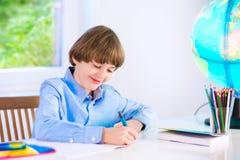 Uśmiechnięta urocza chłopiec robi pracie domowej Zdjęcia Royalty Free
