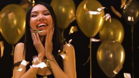 Uśmiechnięta urodzinowa dziewczyna cieszy się przyjęcia pod spada confetti, cukierki szesnaście przyjęcie zbiory wideo