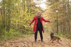 Uśmiechnięta w średnim wieku kobieta w lesie z jej psem Zdjęcie Royalty Free