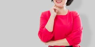 Uśmiechnięta wiek średni kobieta w czerwieni sukni i krzyżować rękach odizolowywających na szarym tle Uzupełniał i piękna pojęcie zdjęcie stock