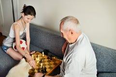 Uśmiechnięta wnuczka i dziadunio bawić się szachy Fotografia Royalty Free