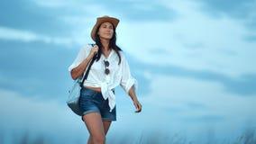 Uśmiechnięta wycieczkowicz podróży kobieta z plecaka odprowadzeniem na lata polu przy zmierzchem zbiory