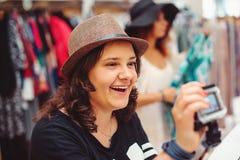 Uśmiechnięte atrakcyjne młode kobiety w kapeluszowym zakupy przy ubrania sklepem tła karciana powitania strony zakupy szablonu cz Zdjęcie Royalty Free