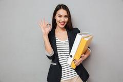 Uśmiechnięte azjatykcie biznesowej kobiety mienia falcówki i seansu ok podpisują Fotografia Stock