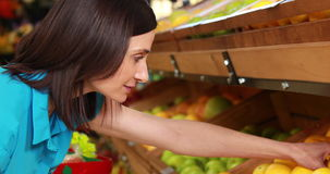 Uśmiechnięte brunetki kładzenia cytryny w zakupy koszu zbiory