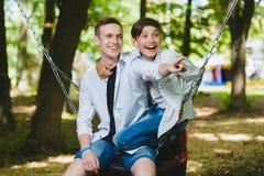 Uśmiechnięte chłopiec ma zabawę przy boiskiem Dzieci bawić się outdoors w lecie Nastolatkowie jedzie na huśtawkowym outside fotografia stock