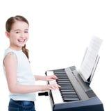 Uśmiechnięte dziewczyn sztuki na elektrycznym pianinie. Obraz Royalty Free