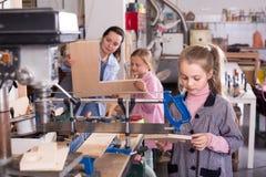 Uśmiechnięte dziewczyny ćwiczy umiejętności przy drewnianym cyzelowaniem Fotografia Stock