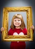 Uśmiechnięte dziewczyny patrzeje przez rocznika obrazka ramy Obrazy Royalty Free