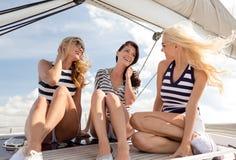 Uśmiechnięte dziewczyny siedzi na jachtu pokładzie zdjęcie stock