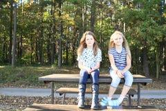Uśmiechnięte dziewczyny siedzi na stole Obrazy Stock