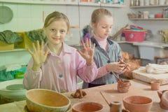 Uśmiechnięte dziewczyny trenuje robić ceramics podczas sztuk Obraz Royalty Free