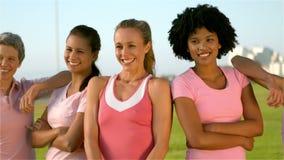 Uśmiechnięte kobiety jest ubranym menchie dla nowotworu piersi zbiory