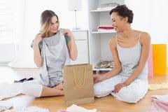 Uśmiechnięte kobiety siedzi na podłoga z torba na zakupy Zdjęcie Stock