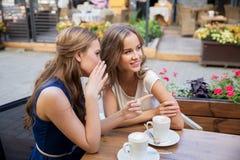 Uśmiechnięte młode kobiety pije kawę i plotkować Zdjęcia Royalty Free