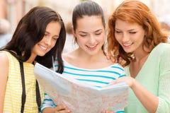 Uśmiechnięte nastoletnie dziewczyny z mapą i kamerą Fotografia Royalty Free