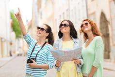 Uśmiechnięte nastoletnie dziewczyny z mapą i kamerą Zdjęcia Stock