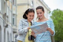 Uśmiechnięte nastoletnie dziewczyny z mapą i kamerą outdoors Fotografia Stock