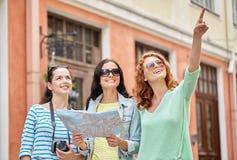 Uśmiechnięte nastoletnie dziewczyny z mapą i kamerą outdoors Zdjęcie Stock