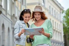 Uśmiechnięte nastoletnie dziewczyny z mapą i kamerą outdoors Zdjęcie Royalty Free