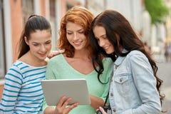 Uśmiechnięte nastoletnie dziewczyny z pastylki kamerą i komputerem osobistym fotografia royalty free